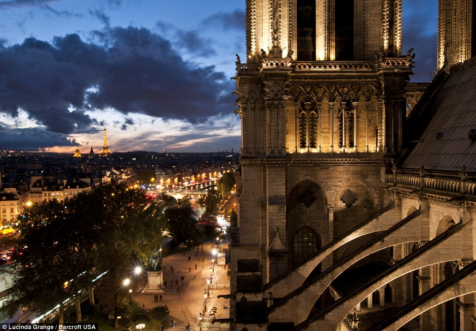 Glowing: A picture of Notre Dame cathedral at night with the Eiffel Tower in the distance