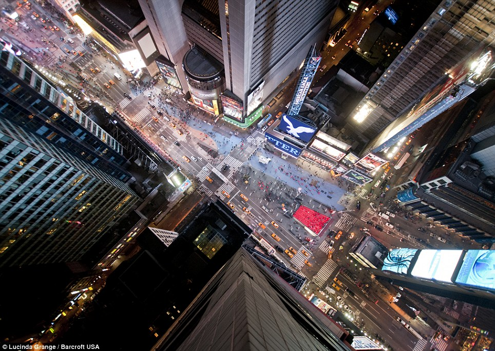 Don't look down: Ms Grange risks life and limb taking picture from the top of Times Square in New York